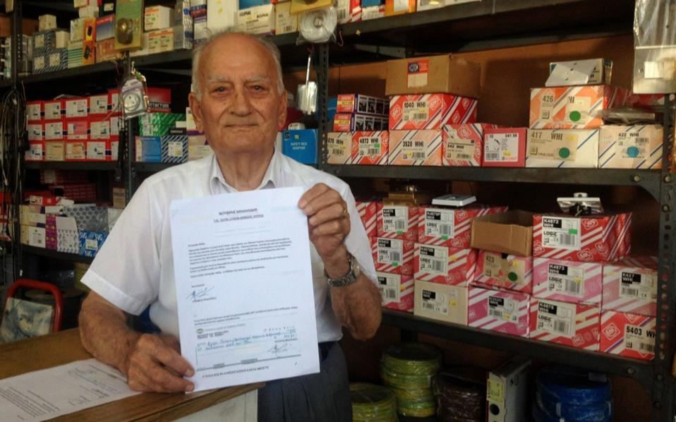 Cypriot shop owner Onoufrios Michaelides, stands in his small electrical appliance store in Cyprus' coastal port city of Limassol on Tuesday holding a letter addressed to Greek Prime Minister Alexis Tsipras, with a check attached donating his monthly pension to Greece, to contribute towards funds to help the country in it's bid to overcome their economic crisis.