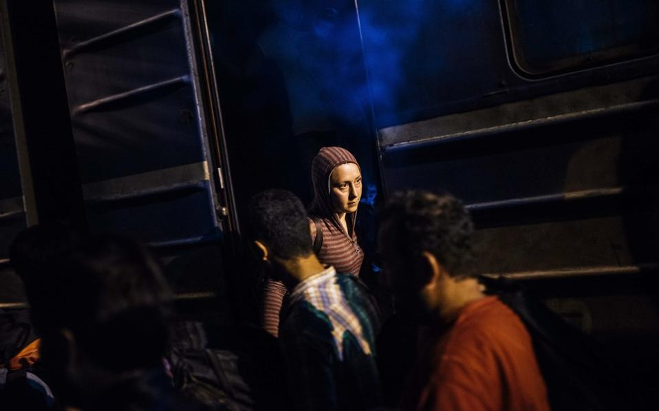 A migrant woman gets out of a train at a railway station on  the Tabanovce border crossing between FYROM and Serbia, on July 1, on her way north to European countries.