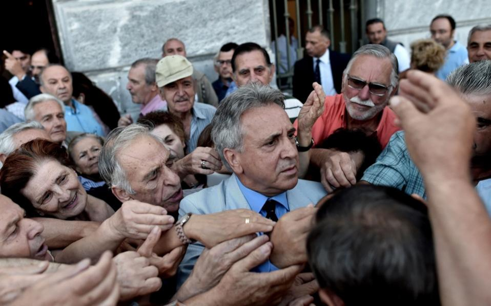 The manager of a National Bank branch delivers priority numbers to pensioners, as banks only opened for the retired to allow them to cash up to 120 euros, in Athens on Wednesday.