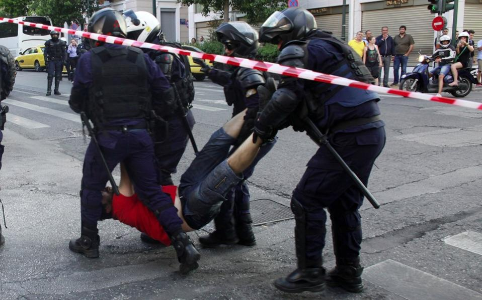 Riot police detains a demonstrator before a rally organized by supporters of the 'No' vote in Athens, on Friday.