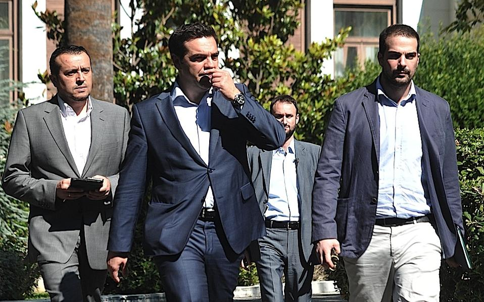 Greece's Prime Minister Alexis Tsipras, center, leaves after a meeting with Greek political party leaders at the Presidential Palace as Minister of State Nikos Pappas, left, and government spokesman Gavriil Sakellaridis, right, follow him in Athens, on Monday.