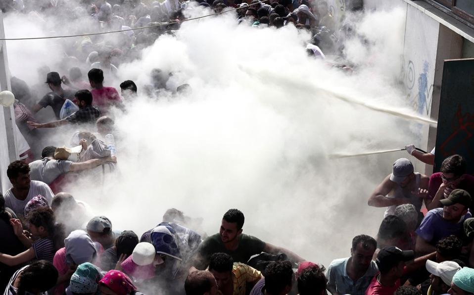 Policemen try to disperse hundreds of migrants by spraying them with fire extinguishers, during a registration procedure which was taking place at the stadium of Kos town, on the southeastern island of Kos, Tuesday.
