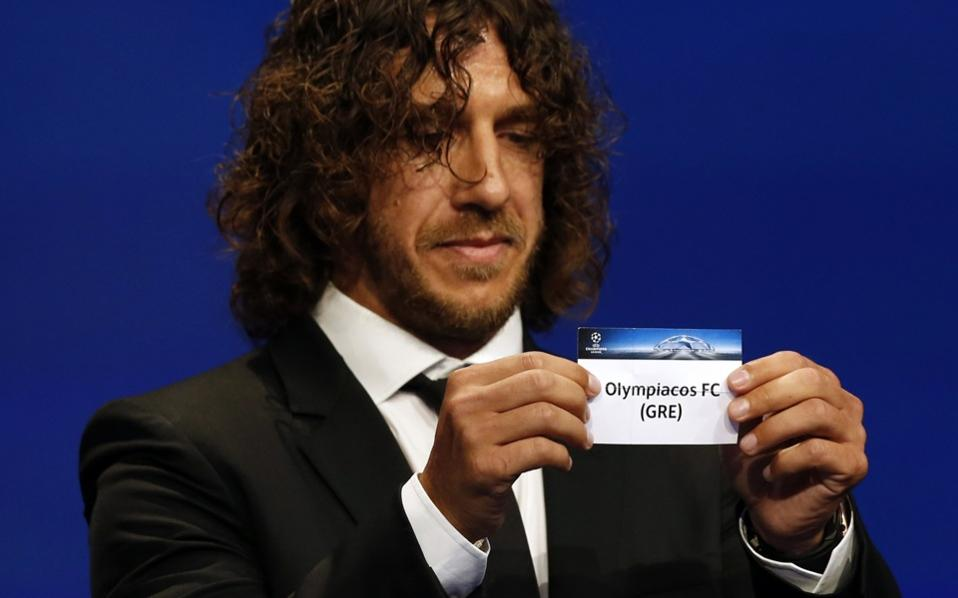 Former Spanish central defender Carlos Puyol shows the name of Olympiacos football club during the UEFA Champions League Group stage draw ceremony, on Thursday.