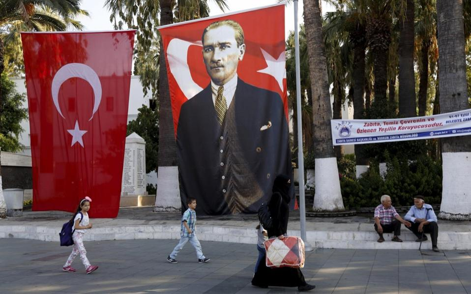 A Syrian woman and her children walk past a Turkish flag and a banner of modern Turkey's founder Ataturk in the resort town of Bodrum, Turkey, Friday.