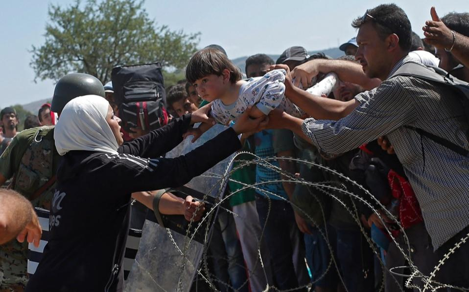 Refugees lift a child across the border between the Greece and FYROM, on Wednesday.
