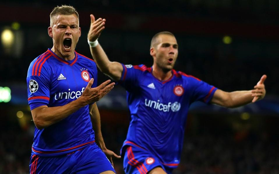 Olympiakos's Alfred Finnbogason (left) celebrates after scoring his side's third goal during the Champions League Group F soccer match between Arsenal and Olympiakos at Emirates stadium in London Tuesday.