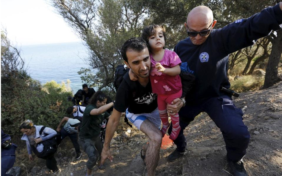 A Greek policeman helps Syrian refugees climb a steep cliff after suspected smugglers dropped them off at a remote beach on the island of Lesvos on Sunday.
