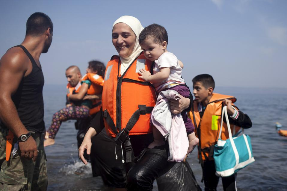 A Syrian refugee holds a child moments after arriving on a dinghy on the Greek island of Lesvos, Thursday.