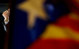 Catalonia's regional government president and leader of the Catalan Democratic Convergence (CDC) Artur Mas behind a pro independence Catalan flag gives the thuimbs up after the announcement of partial results for the regional election, in Barcelona on September 27.