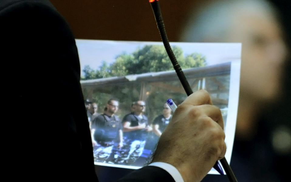 A lawyer for the prosecution holds up a photograph as evidence while questioning a witness at the trial of Golden Dawn in Korydallos, Piraeus, on Thursday.