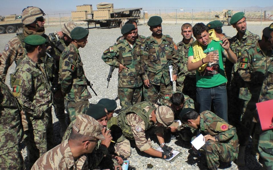 Rameen (right, in civilian clothes) is seen at left with Greek and Iraqi officers during a training session in Kabul in April 2010.