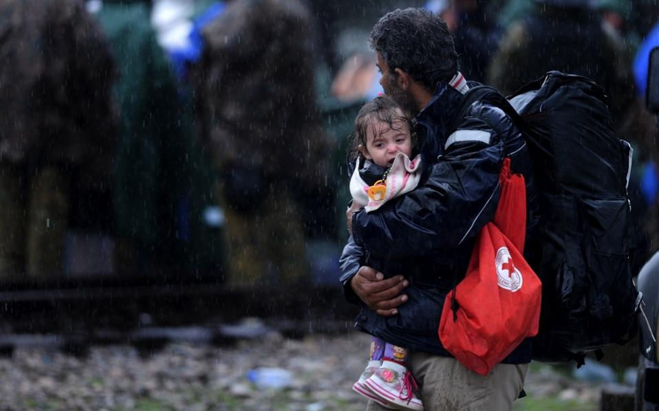 A migrant holds his crying child after crossing the border from Greece to the Former Yugoslav Republic of Macedonia, on Friday, as weather conditions across the region took a turn for the worse.
