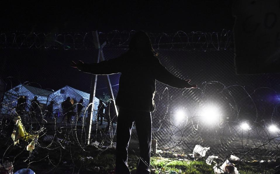 A man stands in front of the border fence, as migrants from Morocco demand to cross the Greek-FYROM border, near the northern Greek village of Idomeni, Monday.