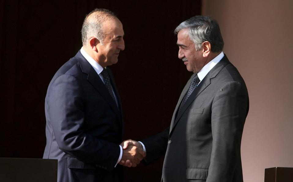 Turkey's Foreign Minister Mevlut Cavusoglu (l) shakes hands with Turkish Cypriot leader Mustafa Akinci during a visit to the breakaway state in the Turkish-occupied part of the island.