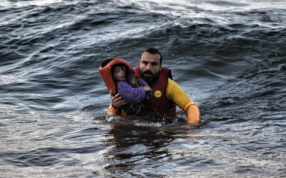 A Spanish lifeguard rescues a child from a boat that sank on October 30 off the coast of Lesvos.