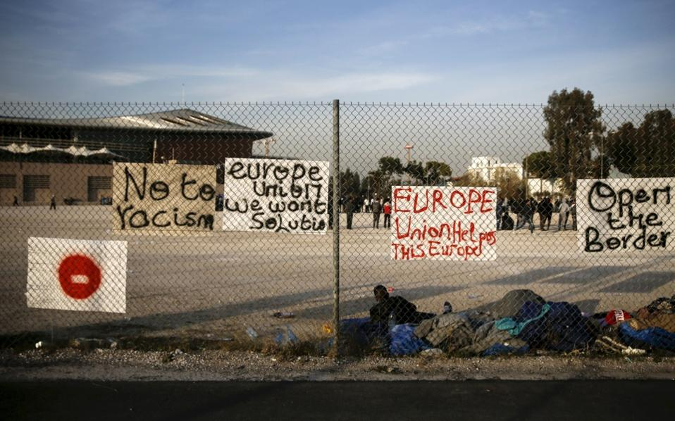 Migrants who were stranded between Greece and the Former Yugoslav Republic of Macedonia, rest next to placards hung on a metal fence, outside the Tae Kwon Do stadium at the southern suburb of Faliro, in Athens, on Monday.