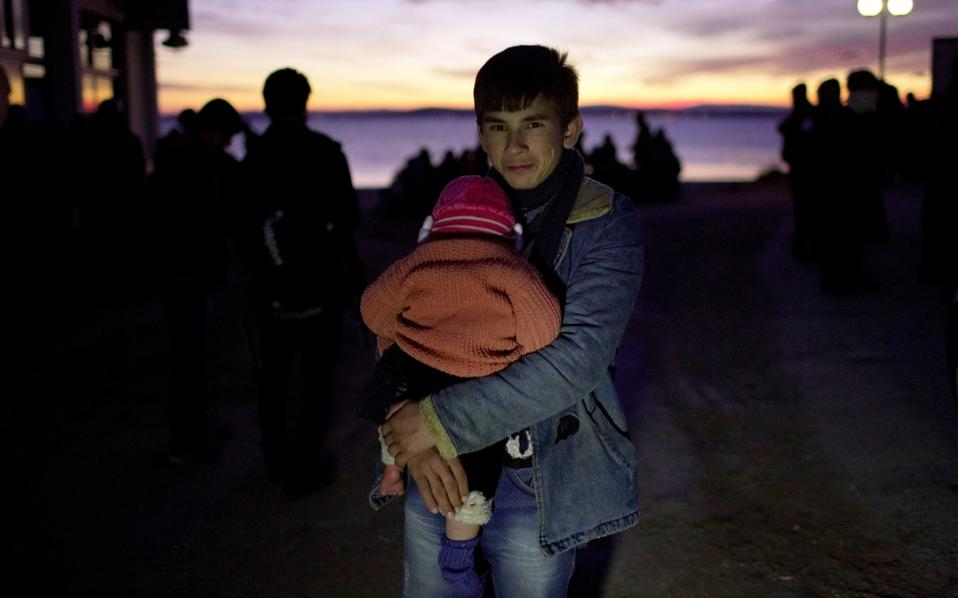 A young Afghan man carries a baby after their arrival from Turkey to the  shores of the Greek island of Chios, on an dinghy overcrowded by refugees and migrants on Friday.