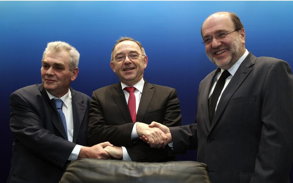 North Rhine-Westphalia Finance Minister Norbert Walter-Borjans (center) shakes hands with Alternate Justice Minister for Corruption Nikos Papangelopoulos (left) and Alternate Finance Minister Tryfon Alexiadis, after signing a joint declaration of intent, in Athens, on Saturday.
