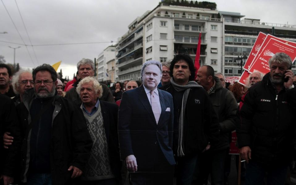 Protesters parade a cardboard cut-out of Labor Minister Giorgos Katrougalos around central Athens on Saturday during a demonstration against the government's pension reform proposals.
