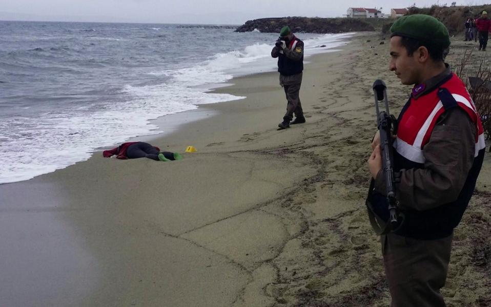 Turkish soldiers take photos of the body of a migrant washed up ashore in Izmir's Dikili district on Tuesday.