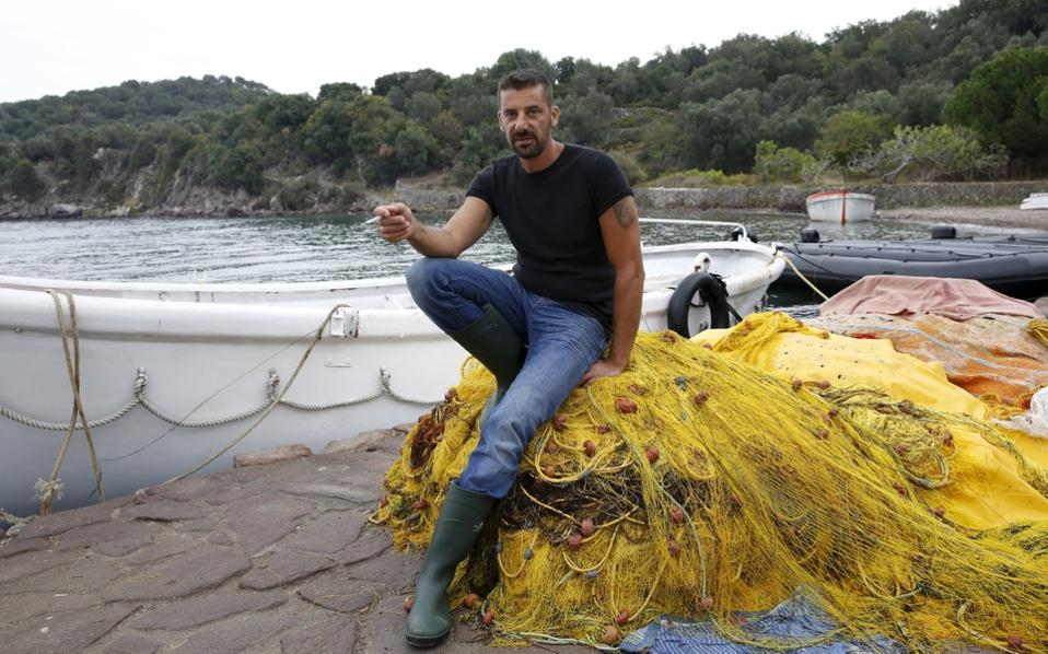 Greek fisherman Stratis Valiamos takes a break at the port of a fishing village on the Greek island of Lesvos, in October 21.