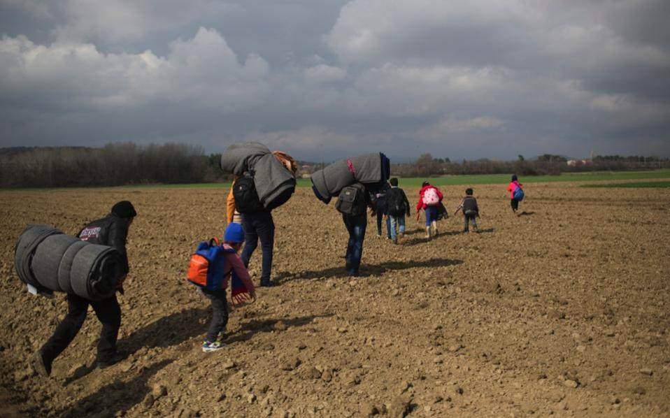 Syrian refugees walk through fields while approaching the Greek border station of Idomeni on Friday.