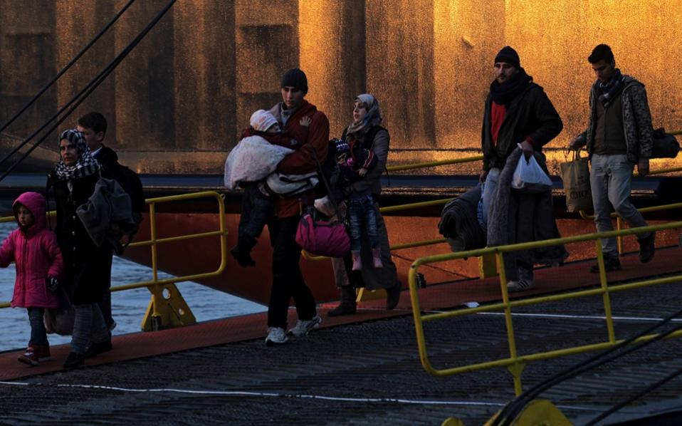 Refugees and migrants disembark from a ferry at the port of Piraeus coming from the island of Lesvos, on Wednesday.