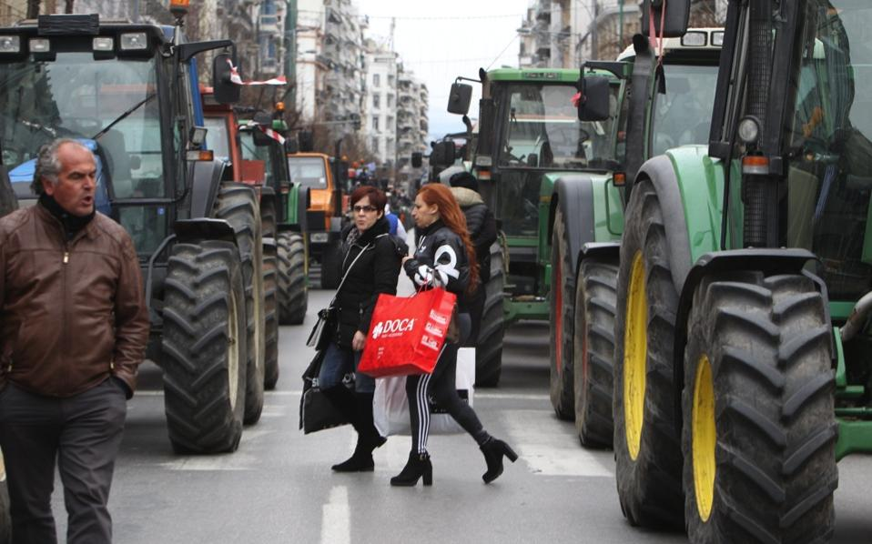 Two women walk between tractors parked along the on of the high streets in Thessaloniki, northern Greece, on Friday.
