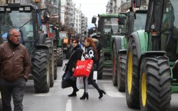 Two women walk between tractors parked along one of the high streets of Thessaloniki, northern Greece, on Friday.