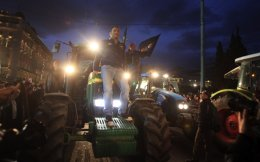 A farmer rides on the front of a tractor as it is driven into Syntagma Square in front of the Parliament in Athens on Friday night. Seventeen tractors were allowed to enter the city center to take part in the protest.