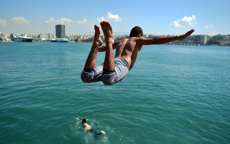 A refugee jumps in the sea near a makeshift camp for refugees and migrants in Piraeus, on Wednesday.