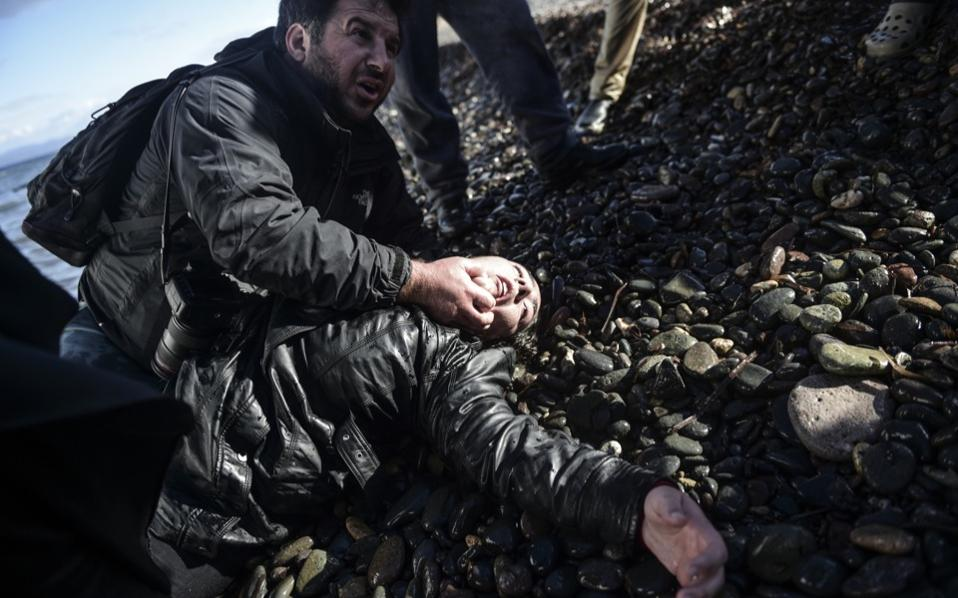 Greek photojournalist Giorgos Moutafis assists an injured woman lying on the shore after she arrived with other migrants and refugees on the island of Lesvos after crossing the Aegean Sea from Turkey on November 26. [AFP]