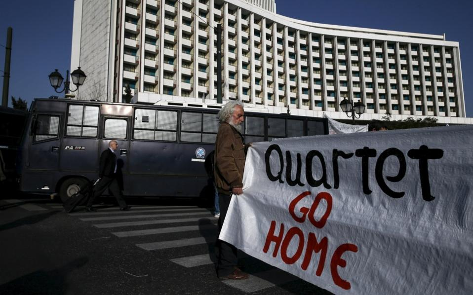 A protester holds a banner during a demonstration outside a central hotel where Greek Finance Minister Euclid Tsakalotos was meeting with the representatives of the country's international lenders, in Athens, on Monday.
