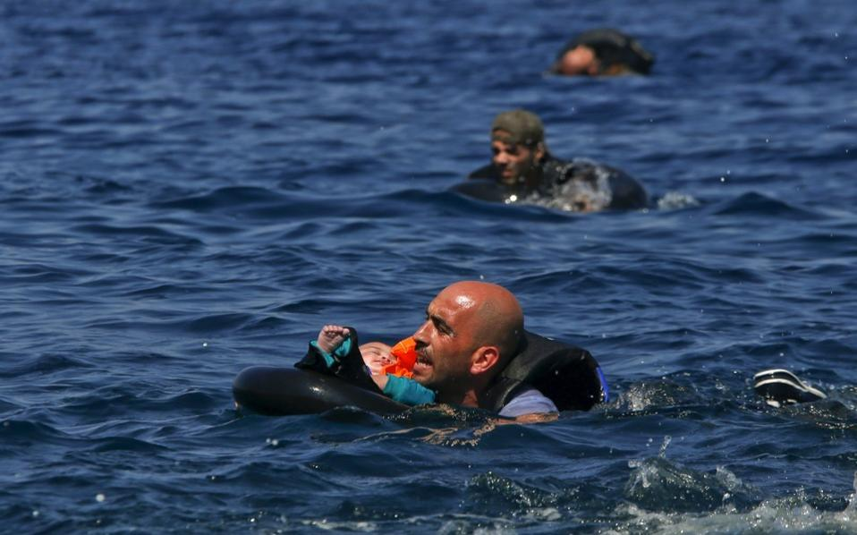 A Syrian refugee holding a baby in a life tube swims towards the shore after their dinghy deflated some 100m away before reaching the Greek island of Lesvos, September 13, 2015. [Alkis Konstantinidis]