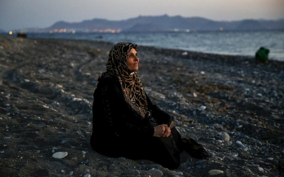 Amoun, 70, a blind Palestinian refugee who lived in the town of Aleppo in Syria, rests on a beach moments after arriving along with another 40 people on a dinghy in the Greek island of Kos, crossing a part of the Aegean Sea from Turkey to Greece, August 12, 2015. [Yannis Behrakis]