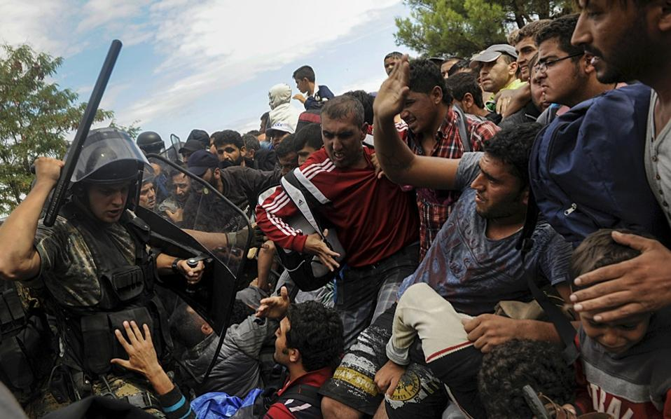 A police officer from the Former Yugoslav Republic of Macedonia (FYROM) raises his baton to migrants to stop them from entering into FYROM at Greece's border near the village of Idomeni, August 22, 2015. [Alexandros Avramidis]
