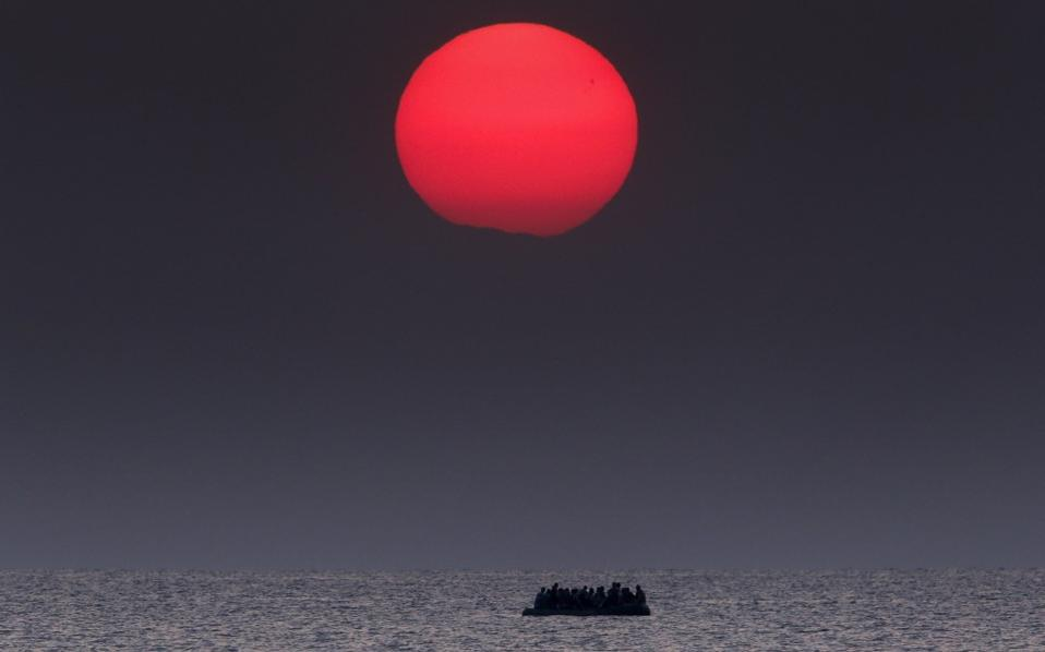 An overcrowded inflatable boat carrying Syrian refugees drifts in the Aegean sea between Turkey and Greece after its motor broke down off the Greek island of Kos, August 11, 2015. [Yannis Behrakis]