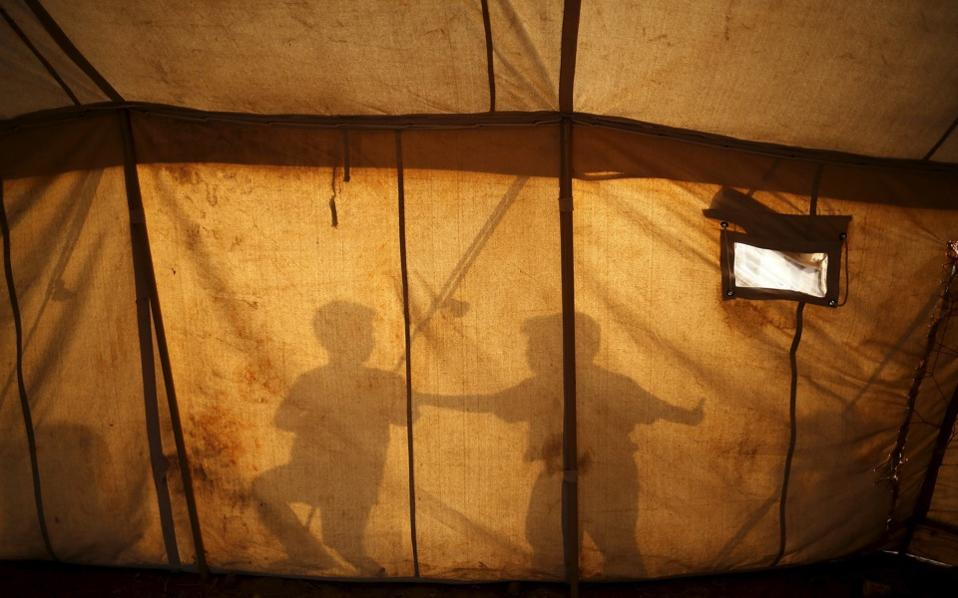 The shadows of children are seen on a tent as they play at a makeshift camp for migrants and refugees at the Greek-FYROM border near the village of Idomeni, on Tuesday.