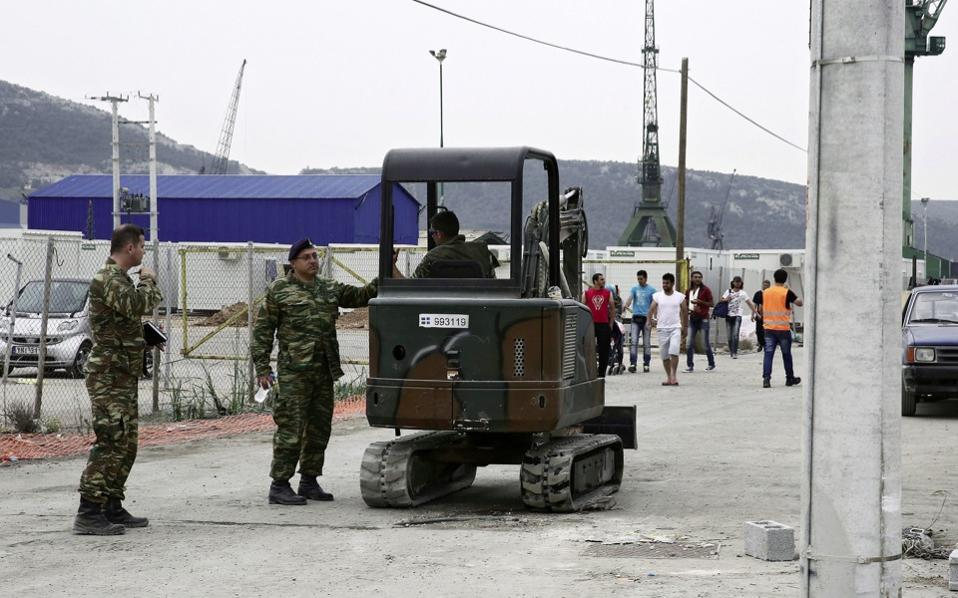 Greek soldiers build basic infrastructure in a new facility in Skaramangas, near Athens, on Thursday.