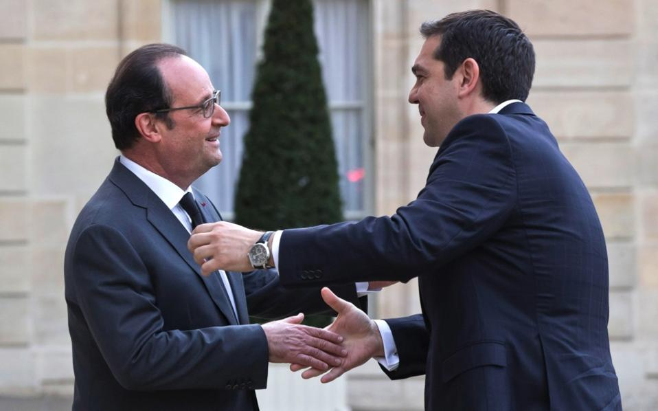 French President Francois Hollande, left, welcomes Greek Prime Minister Alexis Tsipras at the Elysee Palace in Paris, on Wednesday.
