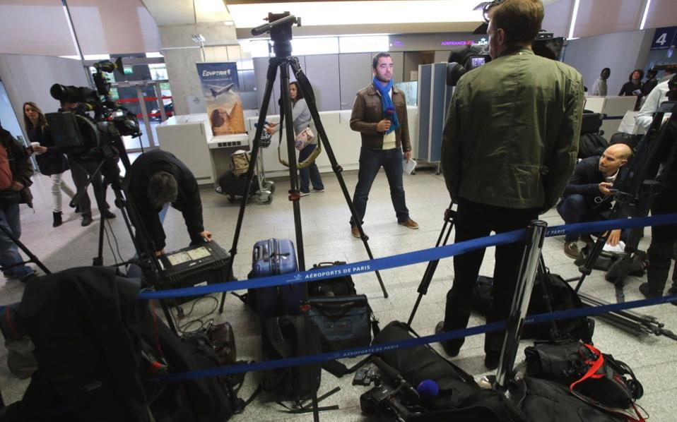 Reporters gather in front of EgyptAir's counter at Charles De Gaulle Airport on Thursday.