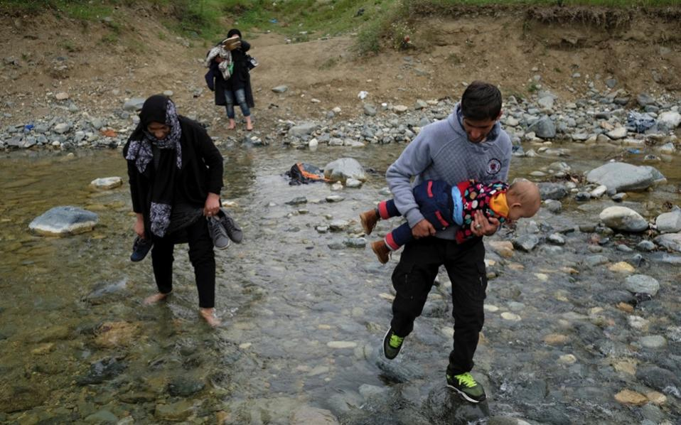 A group of people who tried to breach the Greek border with the Former Yugoslav Republic of Macedonia are seen crossing a small river on their way back to a makeshift camp for refugees and migrants at the border near the village of Idomeni, on Thursday.