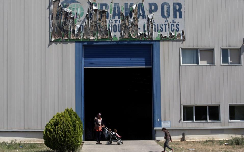 People are pictured at a new camp for refugees and migrants set up in an abandoned factory in Sindos, a suburb in western Thessaloniki, on Friday.