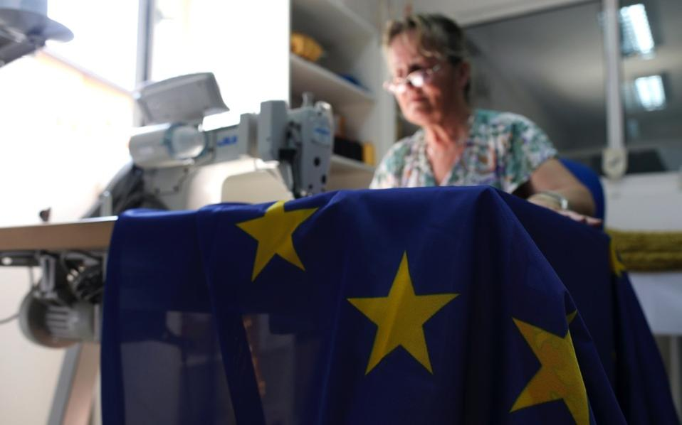 A seamstress sews an EU flag in a workshop in Belgrade, Serbia, Wednesday.