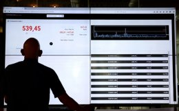 A man watches share price data displayed on an electronic board at the Athens Stock Exchange (ASE), which closed 13.42 percent down after Britain voted to leave the European Union.
