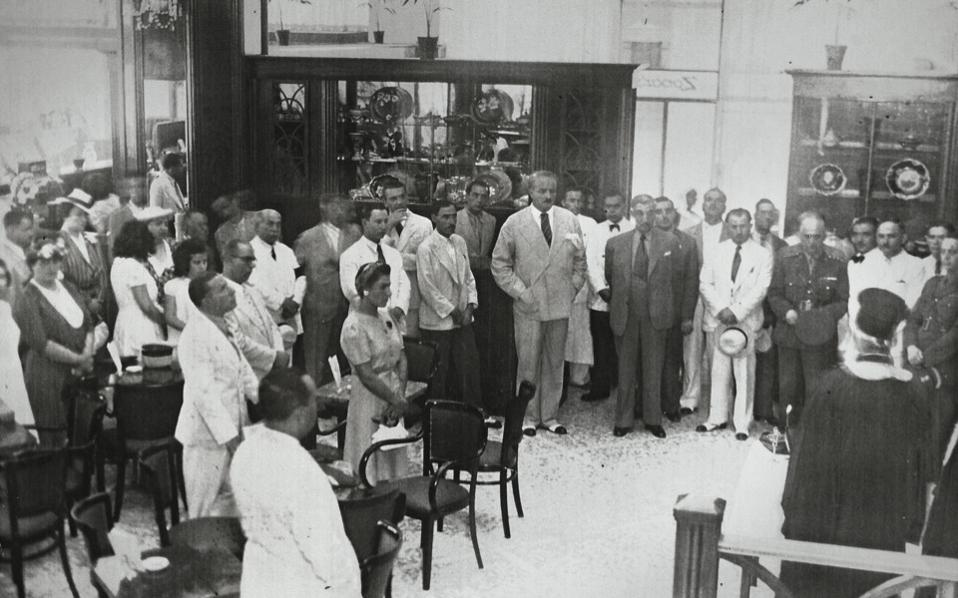 The blessing of Zonars by a priest. The patisserie was inaugurated in August 1940, a week after the Elli was torpedoed, only to close again in April 1941 when Greece was invaded by Nazi Germany.