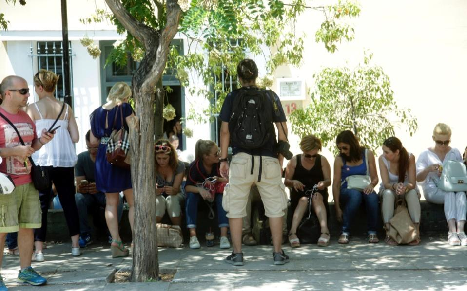 Marinopoulos workers are seen gathered outside the court hearing the case of the supermarket chain's injunction against creditors at the Evelpidon Street court complex in central Athens, on Friday.