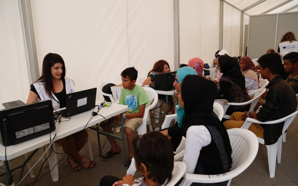 Refugees and migrants are seen during registration at the camp in Elliniko.