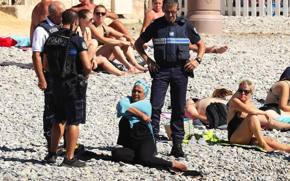 A woman is forced to remove her clothing by French police.