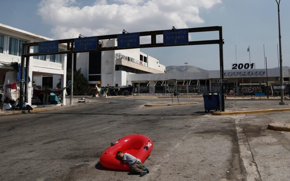 An Afghan boy lays on a plastic boat in the outdoor area of the abandoned former airport in Elliniko, on Athens's southern coast, on Tuesday.